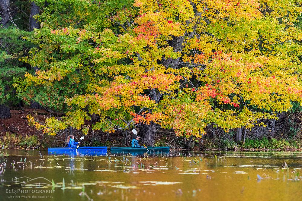 Two women kayaking on Pennesseewassee Lake in Norway, Maine. Fall foliage.