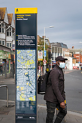 © Licensed to London News Pictures. 12/10/2020. LONDON, UK. A man wearing a facemask passes a street map in Harrow town centre.  It is reported that five London boroughs had more than 100 new COVID-19 cases per 100,000 population in the week to October 8 — Richmond, Hackney, Ealing, Redbridge and Harrow.  As the UK experiences a rise in the number COVID-19 cases nationwide, Boris Johnson, Prime Minister is announcing in the House of Commons a new three-tier local lockdown system to tackle the spread of the virus.  Photo credit: Stephen Chung/LNP