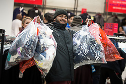 © Licensed to London News Pictures . 26/12/2015 . Manchester , UK . Bargain hunters use clear bags in place of baskets as they shop at Next in Manchester's Arndale Centre , at the start of the annual winter sale . Photo credit: Joel Goodman/LNP
