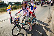 22 DECEMBER 2013 - BANGKOK, THAILAND: An anti-government protestor rides her bike to the home of caretaker Prime Minister Yingluck Shinawatra. Hundreds of thousands of Thais gathered in Bangkok Sunday in a series of protests against the caretaker government of Yingluck Shinawatra. The protests are a continuation of protests that started in early November and have caused the dissolution of the Pheu Thai led government of Yingluck Shinawatra. Protestors congregated at home of Yingluck and launched a series of motorcades that effectively gridlocked the city. Yingluck was not home when protestors picketed her home.     PHOTO BY JACK KURTZ