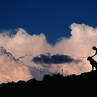A hiker & her dog stand below thunderheads in arid volcanic tablelands near Bishop.