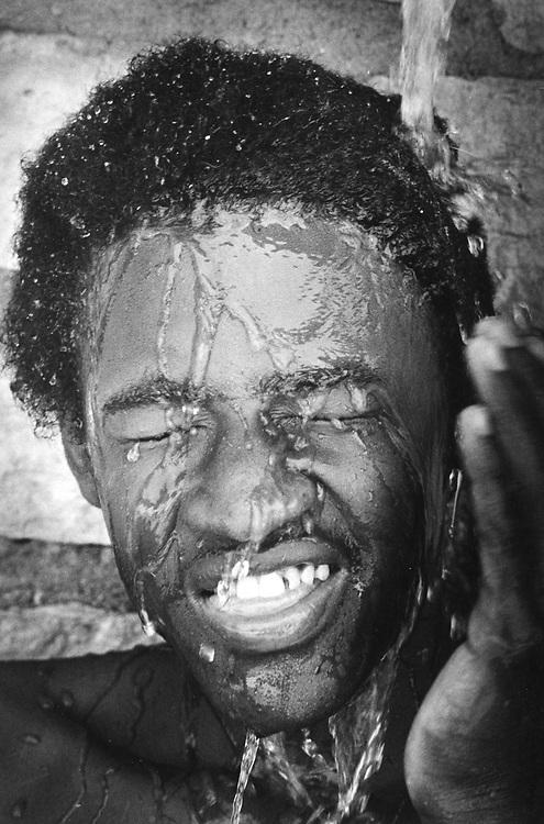 ©1987 black boy cooling off in Texas heat.