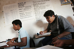 """Maria Ascanio(center),46, and other students participate in a Mision Rivas class in Catia, a poor slum in Caracas. The class is funded by PDVSA and gives people who were unable to finish highschool a chance to earn a highschool equivalency degree. Since the removal of nearly 18,000 workers after an oil strike in Venezuela in 2002, PDVSA, the state run oil company has gone through drastic changes.  Struggling to replace the dismissed workers and return production to pre-strike quantities, PDVSA has also undertaken the financing and coordination of huge social programs.  PDVSA has invested billions of dollars in various education, food, medicine and infrastructure projects, calling itself the """"new"""" PDVSA."""