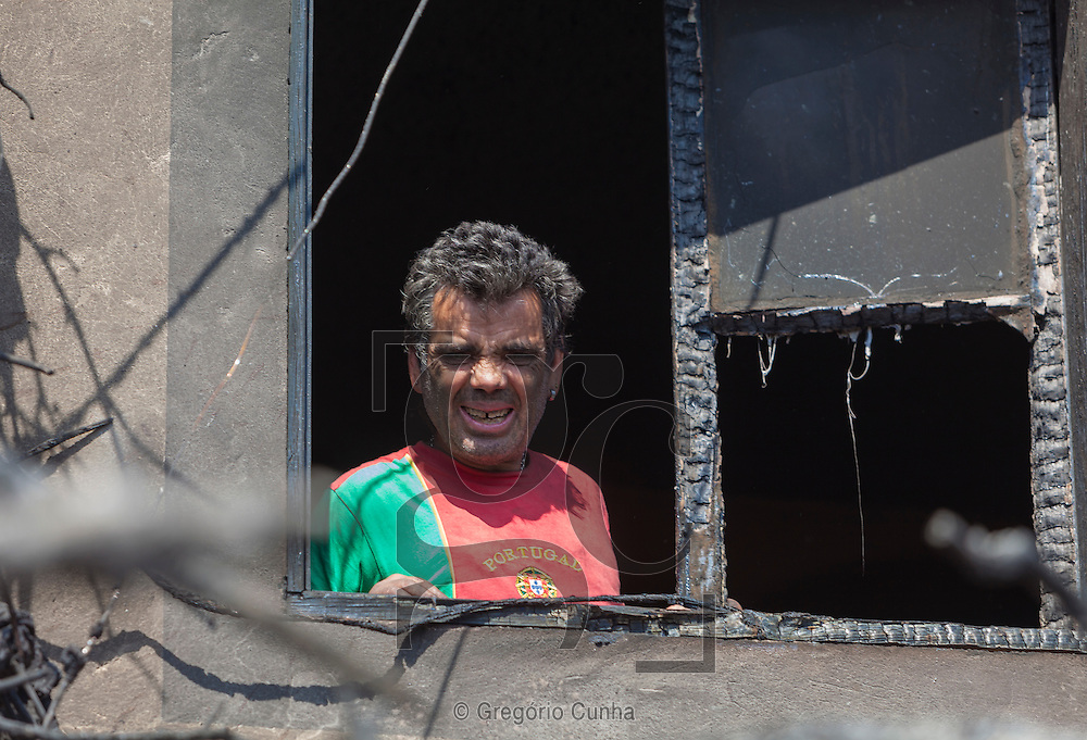 PORTUGAL, Gaula : Jose Nobre stands in his burned house after a fire in Gaula, some 20 km from Funchal on July 20, 2012 on the island of Madeira. Fires raged around the towns of Calheta, Ribeira Brava and Santa Cruz, where one house was destroyed and a health centre, school and youth centre were evacuated as a precautionary measure. The problems began on the evening of July 18 when high temperatures and strong winds fanned a fire that broke out on the edge of the capital Funchal, gutting two houses and partially burning a third. PHOTO / GREGORIO CUNHA