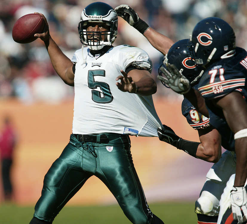 Philadelphia quarterback Donovan McNabb is tugged by Chicago Bears Hunter Hillenmeyer , middle, and Israel Idonije as he throws in the third quarter..