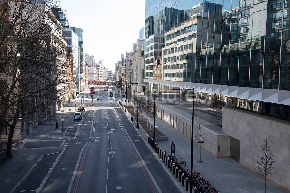 Looking along Farringdon Street on the boundary of the City of London financial district is virtually deserted due to the Coronavirus outbreak on 23rd March 2020 in London, England, United Kingdom. Following government advice city workers are staying at home to work leaving the streets quiet, empty and eerie. Coronavirus or Covid-19 is a new respiratory illness that has not previously been seen in humans. While much or Europe has been placed into lockdown, the UK government has announced more stringent rules as part of their long term strategy, and in particular social distancing.