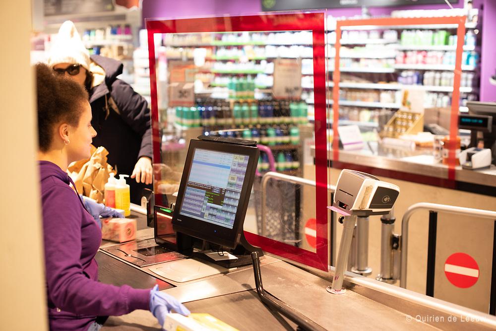 Het RIVM adviseert 1,5 meter afstand tussen mensen. Winkels en supermarkten plaatsen plastic schermen tussen klant en kassamedewerkers ter bescherming.