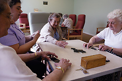 Group of elderly women playing game of dominoes at day centre,