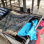 A rack used to dye thread under a weaver's house in northeastern Laos. Finished products (and some clothes drying) sit on top.