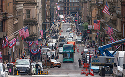 Glasgow, Scotland, UK. 14 July  2021. Filming begins on location in Glasgow city centre for the latest Indiana Jones movie. Filming was taking place on Cochrane Street and final touches were being made to shopfronts on St Vincent Street to convert them into period American stores. Pic; vIew along St Vincent street showing many American flags. Iain Masterton/Alamy Live news.