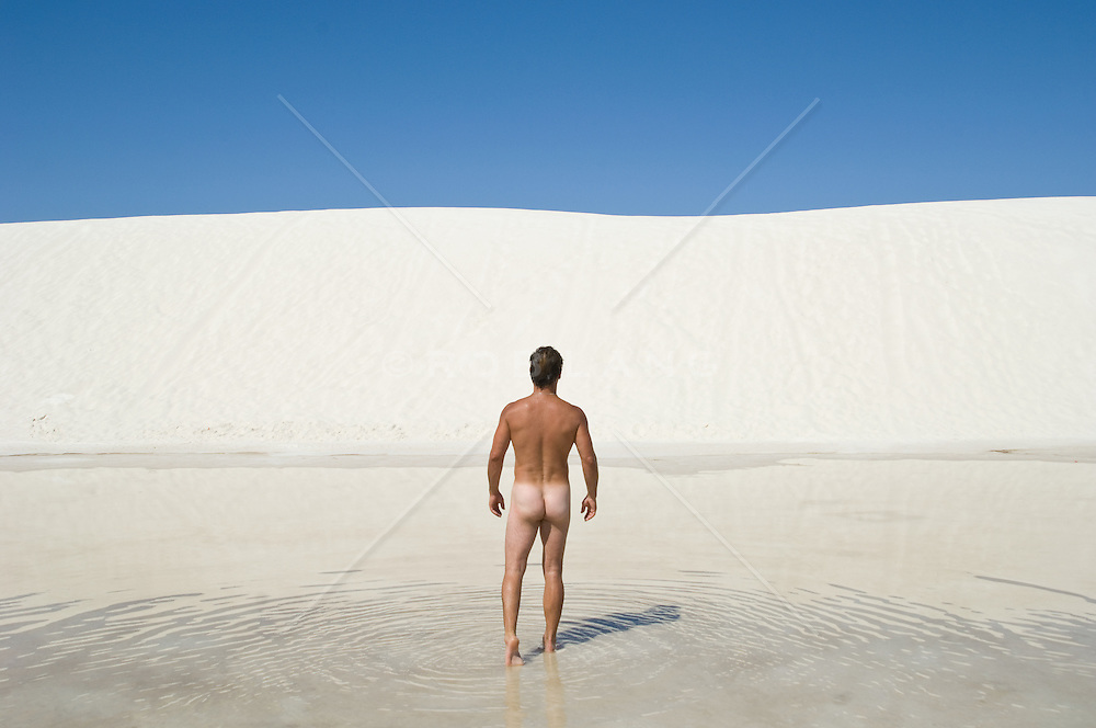 Naked man walking through clear water towards a white sand dune in  White Sands National Park, NM