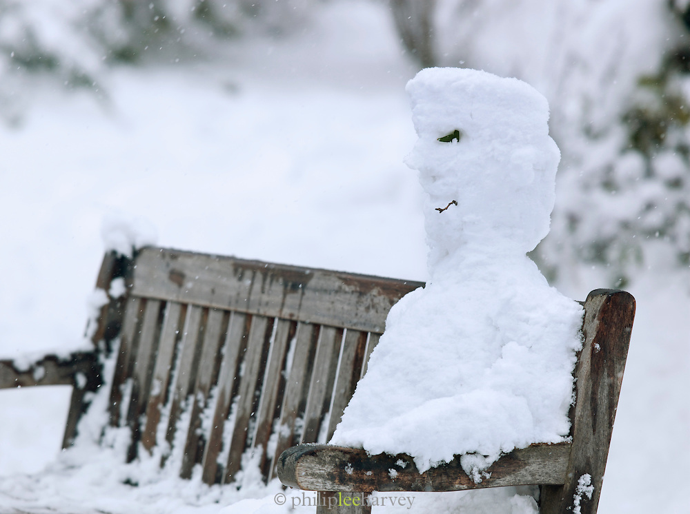 A snowman sitting on a bench in St James Park, London, UK