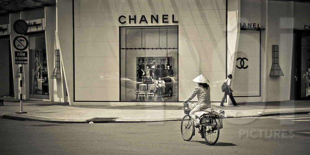 Vietnamese woman riding her bicycle and crossing the street in front of the high luxury Chanel store in Dist.1,  Ho Chi Minh city (HCMC), Vietnam, Asia