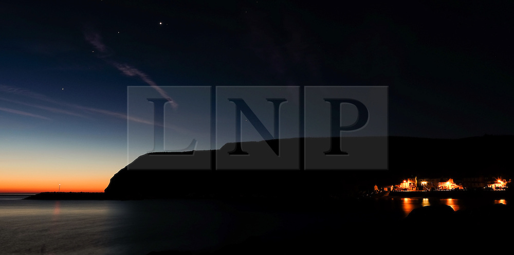 © Licensed to London News Pictures.02/10/15<br /> Staithes, UK. <br /> <br /> Street lights shine on houses as dawn breaks and the constellation Leo sits over cliffs at the North Yorkshire village of Staithes on the east coast as the warm autumn weather continues.<br /> <br /> Photo credit : Ian Forsyth/LNP