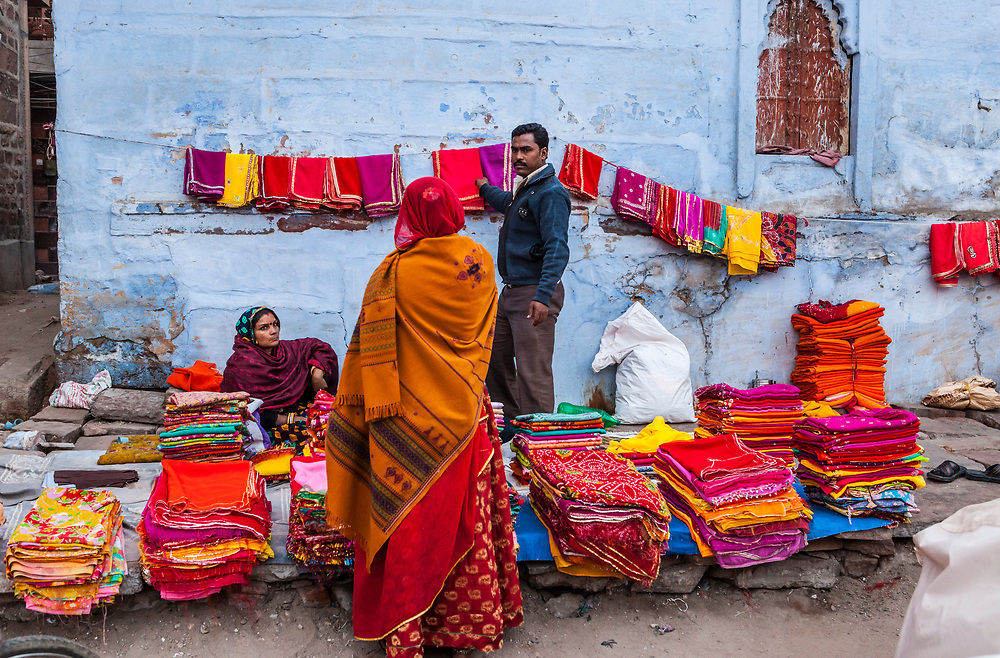A man selling textiles to a customer at an open air street market in Jodhpur, Rajasthan, India.