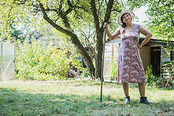 Senior woman with a rake in the garden, Altoetting, Bavaria, Germany