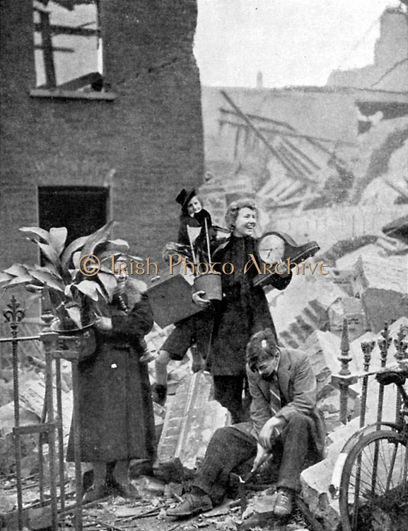 Londoners made homeless by a German bombing raid during the Blitz of 1940 holding some treasured possessions recovered  from the ruins and putting on brave, smiling faces: October 1940. World War II.