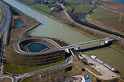Nederland, Limburg, Gemeente Maasgouw,, 07-03-2010; brug over het Julianakanaal tussen Ohe & Laak en Echt. Het kanaal aangelegd in het kader van de Maaskanalisatie ligt tussen dijken en op een aanmerkelijk hoger niveau dan de Maas(rechtsboven) en de snelweg A2 (met oprit, links)..Bridge over the Juliana Canal between Ohe & Laak and Echt. The canal was  was built as part of the Meuse Canalization and lies - between dikes - significantly higher than the Meuse (right) and the A2 highway (with ramp, left)..luchtfoto (toeslag), aerial photo (additional fee required).foto/photo Siebe Swart