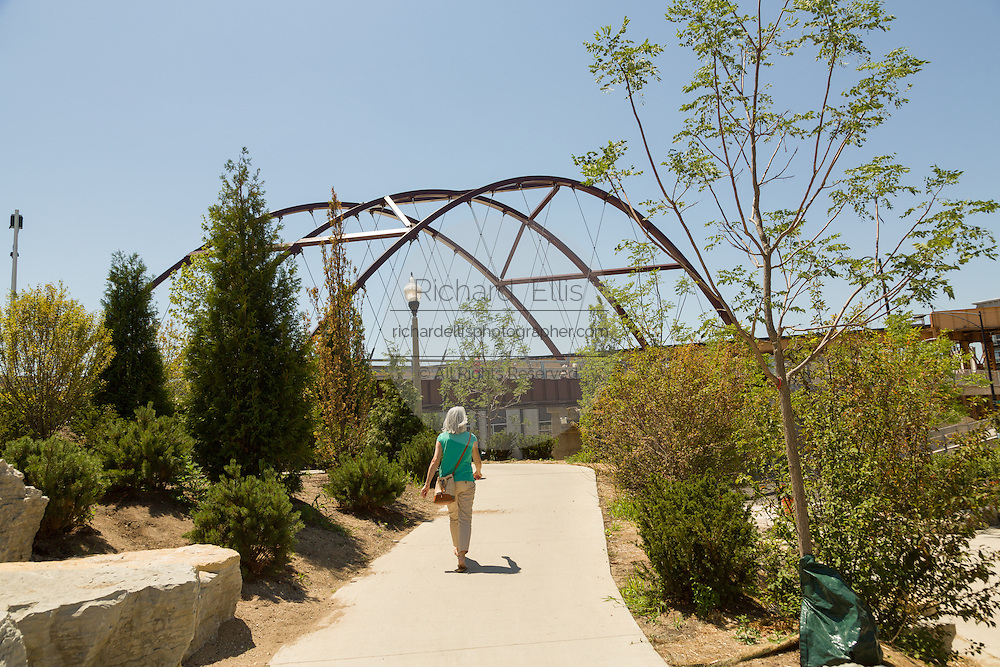 A pedestrian walks toward the Milwaukee Avenue bridge on the 606 elevated bike trail, green space and park built on the old Bloomingdale Line in the Wicker Park neighborhood of Chicago, Illinois, USA