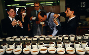 A team of English tea-tasters employed by the tea company Lyons sample different blends for the PG Tips brand in the City of London, England UK. With variously-sourced teas from tea estate plantations, they smell, touch, sip, slurp then spit the hot drink out into a spitoon rather than swallow it many times repeatedly. Britons drink 35 million cups of PG Tips a day and world tea production is approximately 3.2 million tonnes a year. Kenya is the largest producer with Sri Lanka a close second. PG Tips is imported as single estate teas from around the world and blended in precise proportions set by the tea tasters to make blend 777, which can contain between 12 and 35 single estate teas at any one time depending on season.