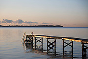 Early morning sun shines on a wooden pier, Oct 29th 2019, Skæring, Denmark. The sea is calm on an early autumn morning. The sea is blue and the wooden pier reflects in the sea. Across the bay is Mols, a part of Denmark opposite Århus.The beach is nearly deserted and is between Århus and the neaby coal power plant Studstrup.