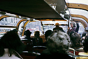 People sitting inside boat trip tour of the city centre Amsterdam, Netherlands 1973 tour guide microphone commentary