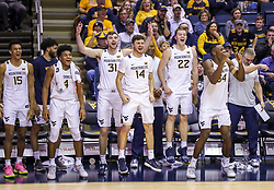 Dec 14, 2019; Morgantown, WV, USA; West Virginia Mountaineers forward Jalen Bridges (15) and West Virginia Mountaineers guard Miles McBride (4) and West Virginia Mountaineers forward Logan Routt (31) and West Virginia Mountaineers guard Chase Harler (14) and West Virginia Mountaineers guard Sean McNeil (22) and West Virginia Mountaineers forward Oscar Tshiebwe (34) celebrates after West Virginia Mountaineers guard Spencer Macke (30) made a free throw late in the second half against the Nicholls State Colonels at WVU Coliseum. Mandatory Credit: Ben Queen-USA TODAY Sports