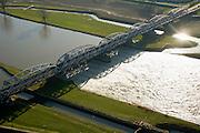 Nederland, Noord-Brabant, Grave, 11-02-2008; stuw in de rivier de Maas, dient om de waterloop te reguleren en het peil te beheren; de Maas is een regenrivier, met met name in de winter grote wateraanvoer (ook door smeltwater); het water rechts (Zuidoostelijk) is hoger; onder in beeld de oude sluiskolk van de schutsluis voor binnenvaartschepen; boven in beeld de nieuw aangelegde vistrap waardoor de vissen langs de stuw stroomopwaarts kunnen zwemmen; de vakwerkbrug is voor de lokale weg over de rivierpeil, kolk, waterpeil, kanalisatie, vispassage, waterhuishouding;..luchtfoto (toeslag); aerial photo (additional fee required); .foto Siebe Swart / photo Siebe Swart