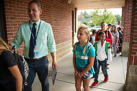 Mr. Bolduc leads his 4th grade students into Elm Street School on Thursday morning to begin their first day of school.  (Karen Bobotas/for the Laconia Daily Sun)