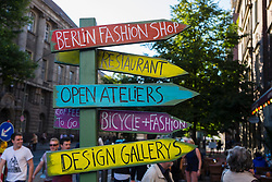 Many hand painted signs pointing to small tourist craft and handwork shops on Oranienburger Strasse in Mitte Berlin Germany