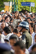 03 FEBRUARY 2013 - PHNOM PENH, CAMBODIA:  A Cambodian girl sits on her father's shoulders while they stand in line to get into the National Museum, site of former King Norodom Sihanouk's crematorium, to pay final respects to their former King. Sihanouk ruled Cambodia from independence in 1953 until he was overthrown by a military coup in 1970. The only music being played publicly is classical Khmer music. Sihanouk died in Beijing, China, in October 2012 and will be cremated during a state funeral royal ceremony on Monday, Feb. 4.    PHOTO BY JACK KURTZ
