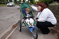 Mother crouching down and chatting to her baby son sitting in his buggy,