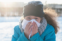 Portrait of girl blowing nose in winter