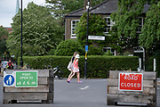 Pedestrians pass through the area that forms an LTN (Low Traffic Neighbourhood), an experimental closure by Southwark Council at the junction of Carlton Avenue and Dulwich Village restrictions also prevent traffic from passing through at morning and afternoon rush-hour times in the borough of Southwark, on 14th June 2021, in London, England.