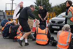 Enfield, UK. 15th September, 2021. Angry motorists prepare to move Insulate Britain climate activists blocking a slip road from the M25 at Junction 25 as part of a campaign intended to push the UK government to make significant legislative change to start lowering emissions. The activists, who wrote to Prime Minister Boris Johnson on 13th August, are demanding that the government immediately promises both to fully fund and ensure the insulation of all social housing in Britain by 2025 and to produce within four months a legally binding national plan to fully fund and ensure the full low-energy and low-carbon whole-house retrofit, with no externalised costs, of all homes in Britain by 2030 as part of a just transition to full decarbonisation of all parts of society and the economy.