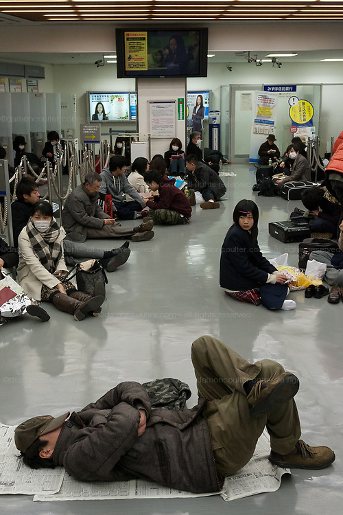People wait in the lobby of a bank to keep warm after a magnitude .9 earthquake hit the Tohoku region of north east Japan causing tremors in Tokyo that stopped the train and cellphone networks. Many people were stranded in the centre of Tokyo over night. Tokyo, Japan Friday March 11th 2011