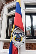 The national flag of Columbia hangs outside the Columbian embassy in Hans Crescent, London SW1. The sign below reads Embajada, Republica de Colombia with the country's crest. This coat of arms contains a shield with numerous symbols. Perched on top of the shield is an Andean Condor holding an olive crown and the condor symbolizing freedom. The national motto, Libertad y Orden (Spanish for Liberty and Order), is on a scroll in between the bird and the shield in black font over golden background. The condor is depicted facing front with his wings extended and looking to the right.