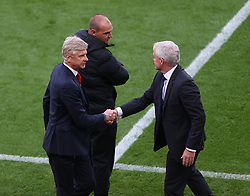 19 August 2017  : Premier League Football : Stoke City v Arsenal:  a final whistle handshake without any eye contact between managers Arsene Wenger of Arsenal (left) and Mark Hughes of Stoke, witnessed by fourth official Bobby Madley: Photo: Mark Leech