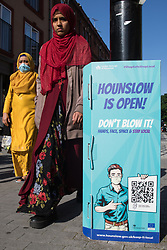 Members of the public pass a London Borough of Hounslow Covid-19 public information sign urging residents to take precautions to minimise the spread of the coronavirus amid rising concern regarding the Delta variant on 17th July 2021 in Hounslow, United Kingdom. The UK government is currently still expected to lift almost all restrictions on social contact on 19th July, known as 'Freedom Day', but the current wave driven by the Delta variant is not expected to peak until mid-August.