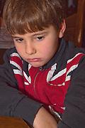 Boy age 7 wearing a UK Union Jack flag shirt feeling a little unhappy. St Paul Minnesota USA