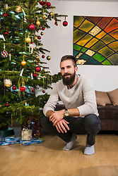 Portrait of young man crouching beside Christmas tree