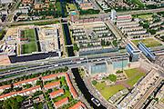 Nederland, Noord-Holland, Amsterdam, 14-06-2012; Ring A10, Einsteinweg. Slotervaart gezien vanuit Bos en Lommer. Rechts Kolenkitbuurt en kerk De Kolenkit (Opstandingskerk) en Poortgebouw. Links van de Eramusgracht de nieuwe wijk Laan van Spartaan. Aan deze zijde van de snelweg het voormalig GAK-gebouw. .De wijk is onderdeel van de Westelijke Tuinsteden, gerealiseerd op basis van het Algemeen Uitbreidingsplan voor Amsterdam (AUP, 1935). Voorbeeld van het Nieuwe Bouwen, open bebouwing in stroken, langwerpige bouwblokken afgewisseld met groenstroken. ..Residential district Slotervaart, one of the western garden cities of Amsterdam-west..  Constructed on the basis of the General Extension Plan for Amsterdam (AUP, 1935). Example of the New Building (het Nieuwe Bouwen), detached in strips, oblong housing blocks alternated with green areas, built in fifties and sixties of the 20th century. The church is nicknamed Kolenkit (coal-hod) and so this district is called the Coal-hod district. A10 Ringroad crosses the neighbourhood. .luchtfoto (toeslag), aerial photo (additional fee required).foto/photo Siebe Swart