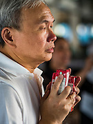 """29 NOVEMBER 2016 - BANGKOK, THAILAND:  A man prays before donating juice boxes to Buddhist monks during a special """"tak bat"""" or merit making ceremony in the Ratchaprasong skywalk of the Bangkok BTS system. The tak bat was to honor Bhumibol Adulyadej, the Late King of Thailand. Food and other goods were given to the monks, who in turn gave the items to charities that will distribute them to Bangkok's poor. More than 100 Buddhist monks participated in the merit making ceremony. The ceremony was organized by the merchants in the Ratchaprasong Intersection, which includes some of Bangkok's most upscale shopping centers.     PHOTO BY JACK KURTZ"""