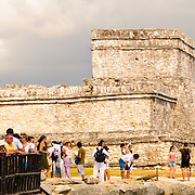 Tourists at the ruins of the Maya civilization city at Tulum look out over the Caribbean sea with El Castillo in the background.