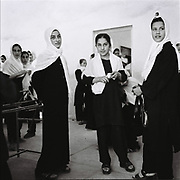 Afghan school girls in a black-and-white uniforms stand in a hallway inside a school which was slightly damaged by a small bomb presumably done by some sort of insurgents who did not want girls to be educated in Panjshir Valley, Afghanistan, Wednesday, Sept. 6, 2006.