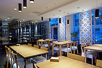 Wide-angle interior view of the dining room of Georgian restaurant Shoti in Kyiv, Ukraine. Glass cabinet of enoteca is on the background. Modern european interior design includes traditional georgian decorative elements.