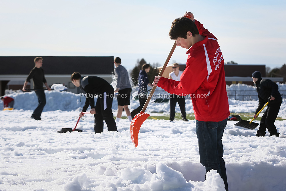(3/13/15, HOLLISTON, MA) Ethan Bagge and other members of the Holliston Ultimate Frisbee team clear the turf field with shovels at Holliston High School on Friday. Various teams have been taking turns clearing the field in an effort to make it usable for the start of spring sports. Daily News and Wicked Local Photo/Dan Holmes