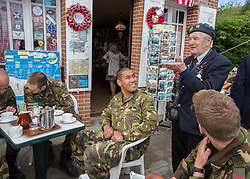 © Licensed to London News Pictures. 29/05/2014. Alan Hartley entertains some Dutch Paratroopers with his stories of the infamous gliders that landed at Pegasus Bridge in the famous Cafe Gondree.  The Cafe has been run by the same family since the D Day Landings and offers free drinks to veterans. Photo credit : Alison Baskerville/LNP