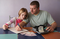 Single parent and young daughter making a shopping list and counting money,