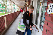 Volunteer Katherine Gilroy posts leaflets for a local community support group called Mutual Aid through letter boxes on a housing estate near the Caledonian Road in North London on 17th March 2020. Mutual Aid and other community support groups have grown significantly in the last few days as people volunteer to help their neighbours who are vulnerable or self isolating with things like shopping, getting prescriptions, and providing meals.  via Getty Images.